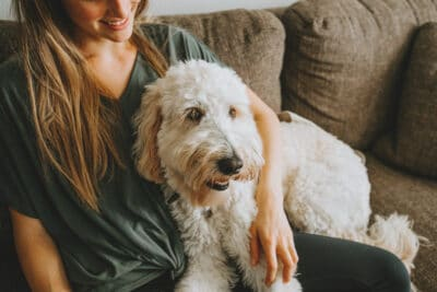 Girl sitting on sofa with fluffy dog at home.